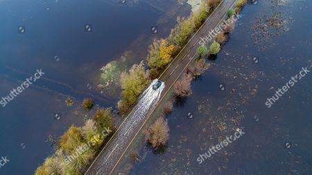 Cars going through a flooded road near Welney in Cambridgeshire after the River Great Ouse burst its banks.