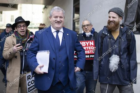 The Scottish National Party's Westminster Leader Ian Blackford talks to Anti Corbyn protesters as he leaves the BBC