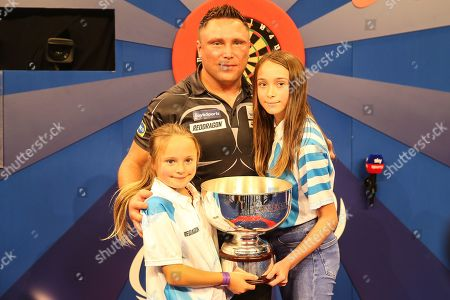 Stock Photo of Gerwyn Price wins and holds aloft The Eric Bristow Trophy with his two daughters during the Grand Slam of Darts, at Aldersley Leisure Village, Wolverhampton