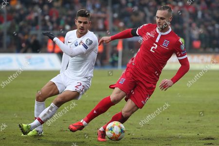 Portugal's Andre Silva, left, and Luxembourg's Maxime Chanot fight for the ball during the Euro 2020 group B qualifying soccer match between Luxembourg and Portugal at the Josy Barthel stadium in Luxembourg