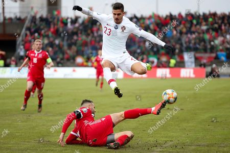 Portugal's Andre Silva, top, jumps over Luxembourg's Maxime Chanot during the Euro 2020 group B qualifying soccer match between Luxembourg and Portugal at the Josy Barthel stadium in Luxembourg
