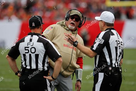 Stock Image of Tampa Bay Buccaneers head coach Bruce Arians questions field judge Aaron Santi (50) and referee Bradley Rogers (126) during the first half of an NFL football game against the New Orleans Saints, in Tampa, Fla