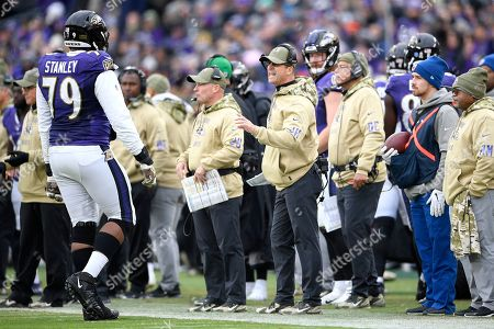 Stock Photo of Baltimore Ravens head coach John Harbaugh, center, talks to offensive tackle Ronnie Stanley (79) during the second half of an NFL football game against the Houston Texans, in Baltimore