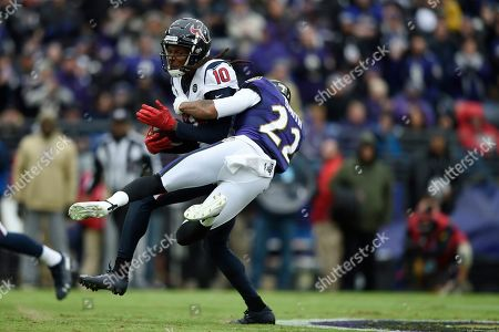 Houston Texans wide receiver DeAndre Hopkins (10) tries to stay up as Baltimore Ravens cornerback Jimmy Smith (22) wraps him up during the first half of an NFL football game, in Baltimore