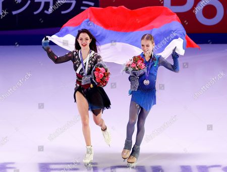 Silver medalist Russia's Evgenia Medvedeva, left, and gold medalist Alexandra Trusova, hold a Russian National flag during an awarding ceremony prior to the exhibition gala at the Rostelekom Cup ISU Grand Prix of figure skating event, in Moscow, Russia