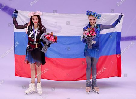 Stock Picture of Silver medalist Russia's Evgenia Medvedeva, left, and gold medalist Alexandra Trusova, hold a Russian National flag during an awarding ceremony prior to the exhibition gala at the Rostelekom Cup ISU Grand Prix of figure skating event, in Moscow, Russia