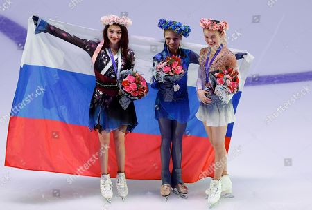 Stock Photo of From left: Silver medalist Russia's Evgenia Medvedeva, gold medalist Alexandra Trusova, and bronze medalist Mariah Bell of the United States pose for a photo during an awarding ceremony prior to the exhibition gala at the Rostelekom Cup ISU Grand Prix of figure skating event, in Moscow, Russia