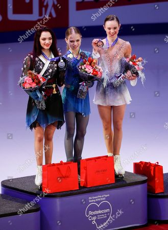 From left: Silver medalist Russia's Evgenia Medvedeva, gold medalist Alexandra Trusova, and bronze medalist Mariah Bell of the United States pose for a photo during an awarding ceremony prior to the exhibition gala at the Rostelekom Cup ISU Grand Prix of figure skating event, in Moscow, Russia