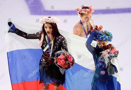 Silver medalist Russia's Evgenia Medvedeva, left, gold medalist Alexandra Trusova, right, and bronze medalist Mariah Bell of the United States prepare to pose for a photo during an awarding ceremony prior to the exhibition gala at the Rostelekom Cup ISU Grand Prix of figure skating event, in Moscow, Russia