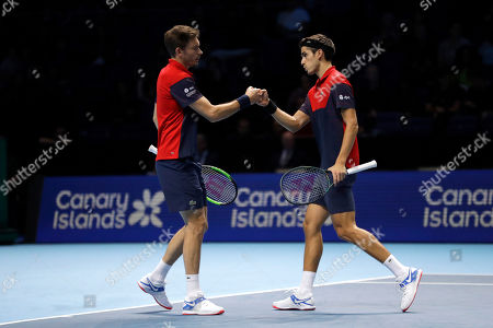 Pierre-Hughes Herbert, right, and Nicolas Mahut of France celebrate winning a point during their ATP World Tour Finals doubles final tennis match against Raven Klaasen of South Africa and Michael Venus of New Zealand at the O2 Arena in London