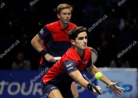 Pierre-Hughes Herbert, right, and Nicolas Mahut of France play a return during their ATP World Tour Finals doubles final tennis match against Raven Klaasen of South Africa and Michael Venus of New Zealand at the O2 Arena in London