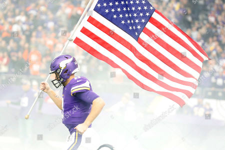 Minnesota Vikings quarterback Kirk Cousins carries a flag onto the field before an NFL football game against the Denver Broncos, in Minneapolis
