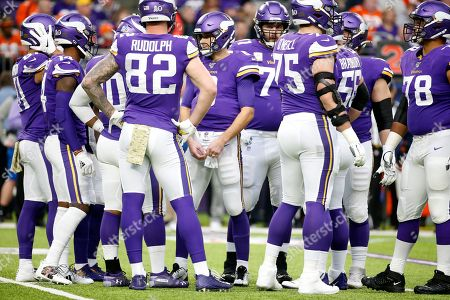 Minnesota Vikings quarterback Kirk Cousins, center, calls a play in the huddle during the first half of an NFL football game against the Denver Broncos, in Minneapolis