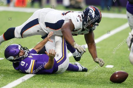 Minnesota Vikings quarterback Kirk Cousins (8) fumbles as he is sacked by Denver Broncos defensive tackle Shelby Harris (96) during the first half of an NFL football game, in Minneapolis