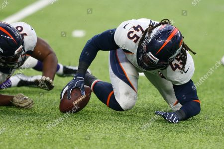 Denver Broncos linebacker A.J. Johnson recovers a fumble by Minnesota Vikings quarterback Kirk Cousins during the first half of an NFL football game, in Minneapolis
