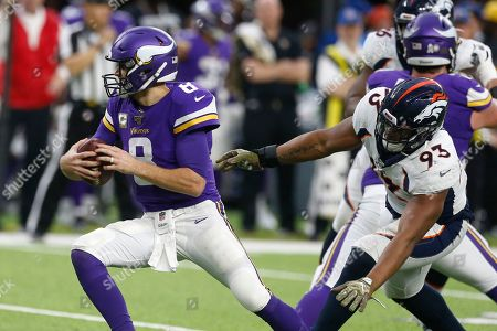 Minnesota Vikings quarterback Kirk Cousins, left, runs from Denver Broncos defensive end Dre'Mont Jones, right, during the second half of an NFL football game, in Minneapolis