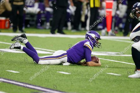Minnesota Vikings quarterback Kirk Cousins rests on the field after getting sacked during the second half of an NFL football game against the Denver Broncos, in Minneapolis