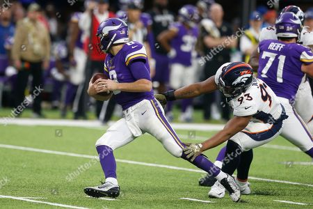 Minnesota Vikings quarterback Kirk Cousins, left, is sacked by Denver Broncos defensive end Dre'Mont Jones, right, during the second half of an NFL football game, in Minneapolis