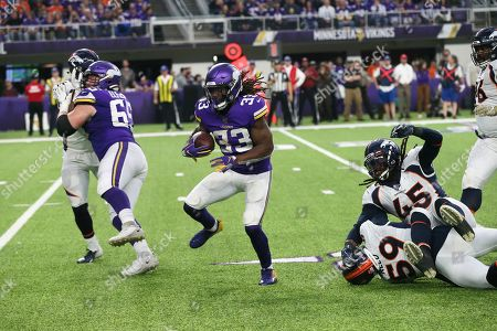 Minnesota Vikings running back Dalvin Cook (33) runs from Denver Broncos defenders Malik Reed (59) and A.J. Johnson (45) during the second half of an NFL football game, in Minneapolis