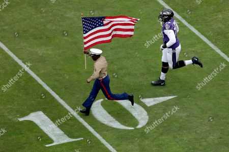 Stock Image of Baltimore Ravens offensive tackle Ronnie Stanley (79) runs with a U.S. service member as part of the team's Salute to Service prior to an NFL football game against the Houston Texans, in Baltimore