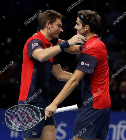 Pierre-Hugues Herbert of France, left and Nicholas Mahut of France celebrate after defeating Raven Klaasen of South Africa and Michael Venus of New Zealand following their ATP World Finals final doubles tennis match at the O2 arena in London