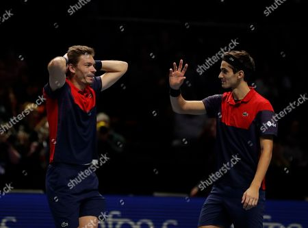 Pierre-Hugues Herbert of France, right, and Nicholas Mahut of France celebrate after defeating Raven Klaasen of South Africa and Michael Venus of New Zealand following their ATP World Finals final doubles tennis match at the O2 arena in London
