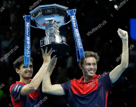 Pierre-Hugues Herbert of France, left, and Nicholas Mahut of France celebrate and hold up the trophy after defeating Raven Klaasen of South Africa and Michael Venus of New Zealand following their ATP World Finals final doubles tennis match at the O2 arena in London