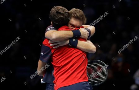 Pierre-Hugues Herbert of France, left and Nicholas Mahut of France hug as they celebrate after defeating Raven Klaasen of South Africa and Michael Venus of New Zealand following their ATP World Finals final doubles tennis match at the O2 arena in London