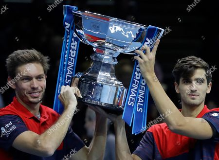 Pierre-Hugues Herbert of France, right, and Nicholas Mahut of France celebrate with the trophy as they pose for photographs after defeating Raven Klaasen of South Africa and Michael Venus of New Zealand following their ATP World Finals final doubles tennis match at the O2 arena in London