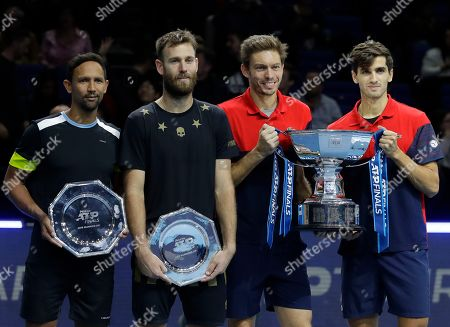 Pierre-Hugues Herbert of France, right, and Nicholas Mahut of France, second right, pose for the media with their winners trophy as Raven Klaasen of South Africa, left, and Michael Venus of New Zealand who hold their runners up plates as the pose for photographs, following their ATP World Finals final doubles tennis match at the O2 arena in London