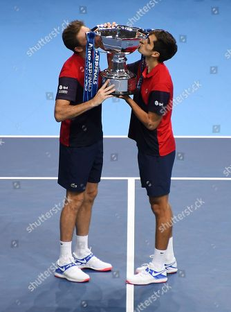 Pierre-Hugues Herbert of France, right, and Nicholas Mahut of France kiss trophy they have won after defeating Raven Klaasen of South Africa and Michael Venus of New Zealand following their ATP World Finals final doubles tennis match at the O2 arena in London