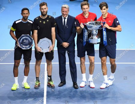Pierre-Hugues Herbert of France, right, and Nicholas Mahut of France, second right, pose for the media with their winners trophy as Raven Klaasen of South Africa, left, and Michael Venus of New Zealand, second left, who hold their runners up plates as the pose for photographs, following their ATP World Finals final doubles tennis match at the O2 arena in London