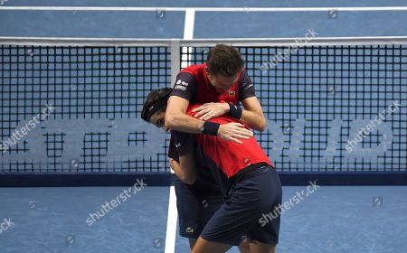 Pierre-Hugues Herbert of France, front left, and Nicholas Mahut of France celebrate after defeating Raven Klaasen of South Africa and Michael Venus of New Zealand following their ATP World Finals final doubles tennis match at the O2 arena in London