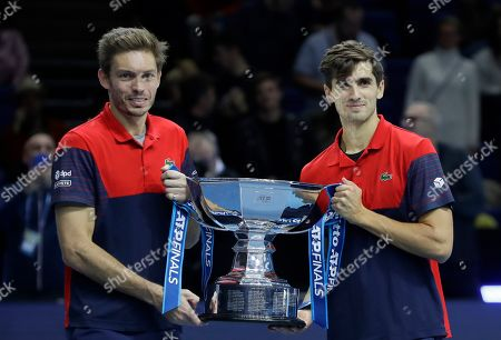Pierre-Hugues Herbert of France, right, and Nicholas Mahut of France pose with their winners trophy for photographs after defeating Raven Klaasen of South Africa and Michael Venus of New Zealand following their ATP World Finals final doubles tennis match at the O2 arena in London