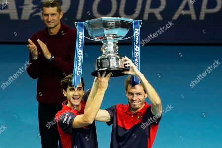 Stock Photo of France's Pierre-Hugues Herbert (C) and Nicolas Mahut (R) pose with their trophy after winning the men's doubles final against New Zealand's Michael Venus and South Africa's Raven Klaasen at the ATP World Tour Finals tennis tournament in London, Britain, 17 November 2019.