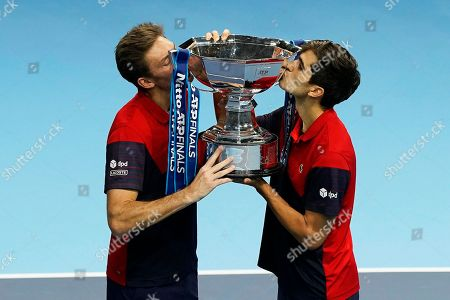 France's Pierre-Hugues Herbert (R) and Nicolas Mahut (L) kiss their trophy after winning the men's doubles final against New Zealand's Michael Venus and South Africa's Raven Klaasen at the ATP World Tour Finals tennis tournament in London, Britain, 17 November 2019.
