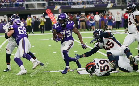 Stock Photo of Dalvin Cook, Malik Reed, A.J. Johnson. Minnesota Vikings running back Dalvin Cook (33) runs from Denver Broncos defenders Malik Reed (59) and A.J. Johnson (45) during the second half of an NFL football game, in Minneapolis