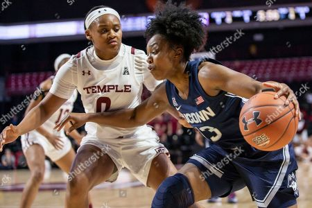 Connecticut guard Christyn Williams (13) moves around Temple guard Ashley Jones (0) during the first half of an NCAA college basketball game, in Philadelphia