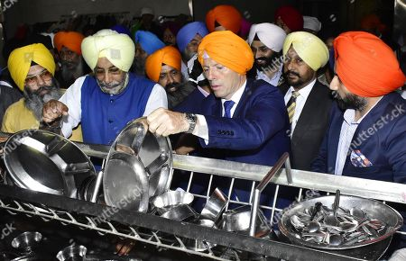 Former Australian Prime Minister Tony Abbott washes utensils at a community kitchen during his visit to the Golden Temple