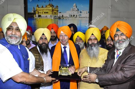 Former Australian Prime Minister Tony Abbott is presented with a memento by members of the Shiromani Gurdwara Parbandhak Committee