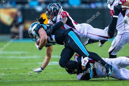Carolina Panthers running back Christian McCaffrey (22) gets tripped up by Atlanta Falcons cornerback Isaiah Oliver (26) and free safety Ricardo Allen (37) in the NFL matchup at Bank of America Stadium in Charlotte, NC