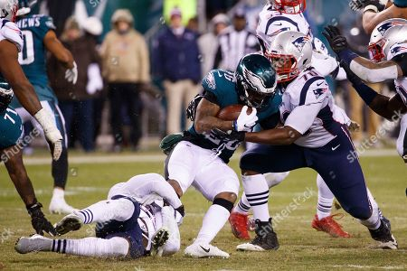 Philadelphia Eagles running back Miles Sanders (26) gets stopped by New England Patriots defensive tackle Adam Butler (70) as he runs with the ball during the NFL game between the New England Patriots and the Philadelphia Eagles at Lincoln Financial Field in Philadelphia, Pennsylvania