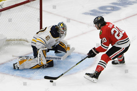 Chicago Blackhawks left wing Brandon Saad (20) skates in on Buffalo Sabres goaltender Carter Hutton (40) during the third period of an NHL hockey game, in Chicago