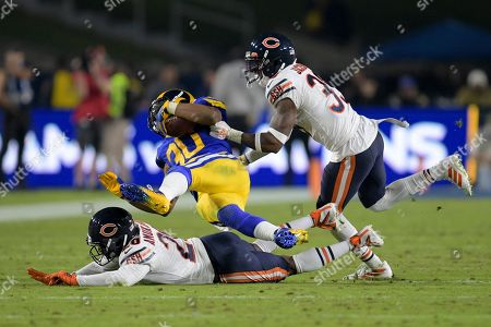 Los Angeles Rams running back Todd Gurley, middle, is tackled by Chicago Bears cornerback Prince Amukamara, bottom, and free safety Eddie Jackson during the second half of an NFL football game, in Los Angeles