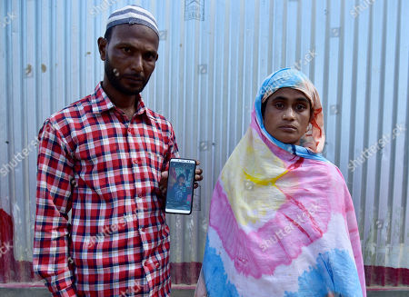 Parents of Minarul Islam(11) showing their son image in mobile as an elephant named after Osama bin Laden has trampled their son to death, at Matia village, in Goalpara district of Assam in India