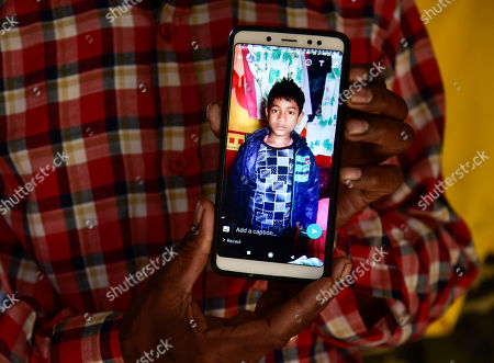 Father of Minarul Islam(11) showing his son image in mobile as an elephant named after Osama bin Laden has trampled his son to death, at Matia village, in Goalpara district of Assam in India