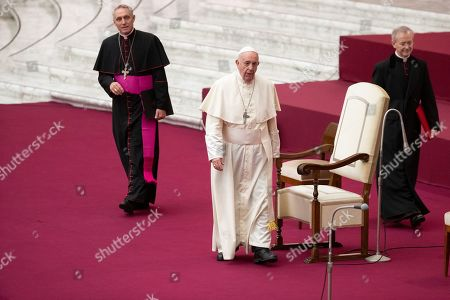 Pope Francis arrives with prefect of the Papal Household Archbishop Georg Gaenswein, left, in the Paul VI Hall at the Vatican for an audience with members of parish evangelization services