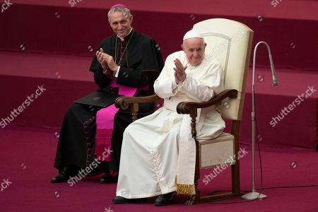 Pope Francis, flanked by Archbishop Georg Gaenswein, applauds in the Paul VI Hall at the Vatican during an audience with members of parish evangelization services
