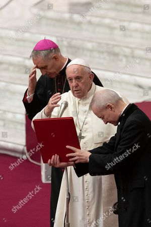 Pope Francis, flanked by Archbishop Georg Gaenswein, delivers his blessing in the Paul VI Hall at the Vatican during an audience with members of parish evangelization services
