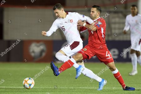 Switzerland's midfielder Christian Fassnacht, left, fights for the ball with Gibraltar's defender John Sergeant, right, during the UEFA Euro 2020 qualifying Group D soccer match between Gibraltar and Switzerland, at the Victoria Stadium, in Gibraltar, 18 November 2019.